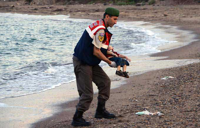 The Iconic photograph of a paramilitary police officer carrying, on September 2, the lifeless body of three-year-old Aylan Kurdi, who died with his mother and brother when boats carrying them and other refugees to the Greek island of Kos capsized near Turkey.