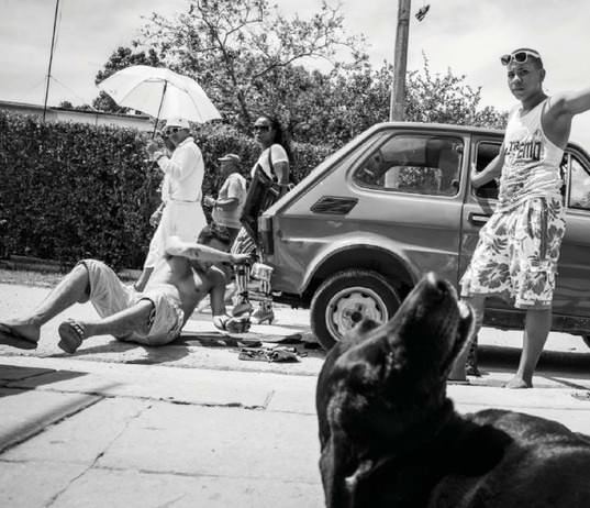 HAVANAS EL COTORRO A typical Cuban street scene can include multiple implied narratives. Here, Lisette Poole captured car repair, strolling neighbors, a Santeria novitiate, and a pet all in a single shot