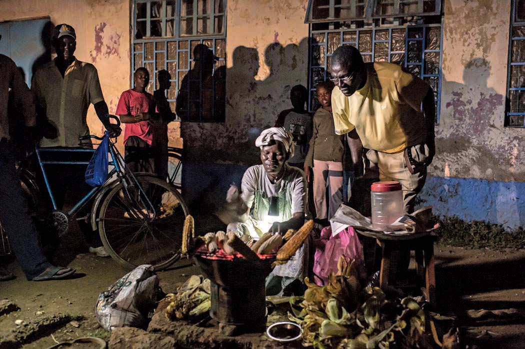 A food vendor in Kisumu cooking by solar-powered light.